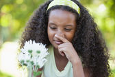Girl holding a flower and covering her nose — Stock Photo