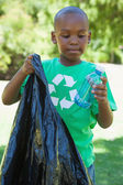 Boy in recycling tshirt picking up trash — Stock Photo