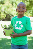Boy in recycling tshirt holding potted plant — Stock Photo