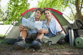 Couple sitting by tent reading a map — Stockfoto