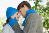 Couple in the park in hats and scarves — Stock Photo