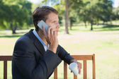 Businessman talking on phone on bench — Stock Photo