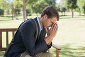 Worried businessman on park bench — Stock Photo