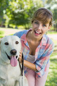 Blonde with her labrador in the park — Stock Photo