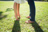 Couples bare feet standing on grass — Stock Photo