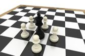 White pawns surrounding black king — Stock Photo