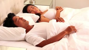 Woman covering ears as partner snoring — Stok video