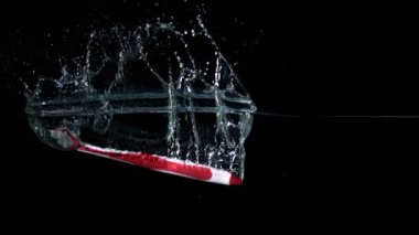 Pink toothbrush falling in water — Stock Video
