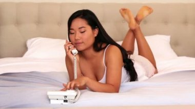 Woman lying on bed talking on phone — Stock Video
