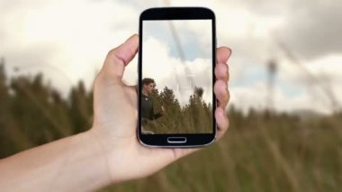 Hand showing adventure clips on smartphone — Vídeo de stock