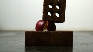 Apple being squashed between bricks — Wideo stockowe
