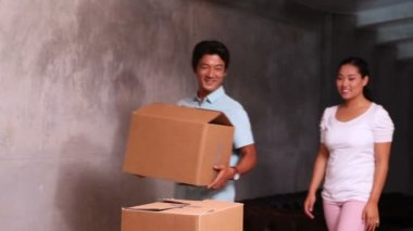 Asian couple unpacking moving boxes — Stock Video