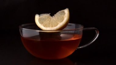 Lemon slice falling in cup of tea — Stock Video