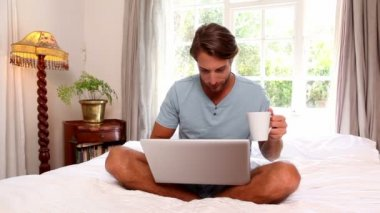 Man using laptop holding mug — Stock Video
