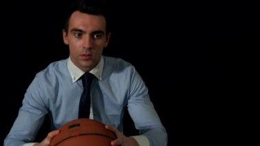 Businessman throwing basketball to camera — Stockvideo