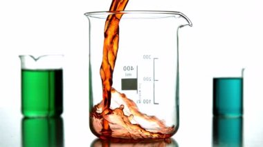 Orange liquid pouring into beaker — Stock Video