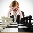 Businesswoman with head in handswith chessboard — Stock Photo #48245653