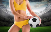 Fit girl holding football — Stock Photo
