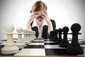 Businesswoman with head in handswith chessboard — Stock Photo