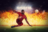 Football player kicking against football pitch — Stock Photo