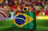 Hand building wall of brazil flag — Stockfoto