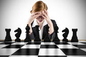 Businesswoman with head in hands with chessboard — Stock Photo