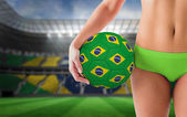 Fit girl holding brazil football — Stock Photo