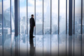 Businessman in room overlooking city — Stock Photo
