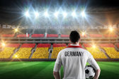 Composite image of germany football player holding ball — Stockfoto
