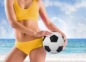 Girl in bikini holding football — Stockfoto