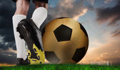 Football boot kicking huge gold ball — Stock Photo