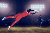 Goalkeeper in red making save — Stock Photo