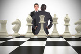 Businessmen and chess pieces — Stock Photo