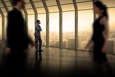 Business people walking in a blur against room — Stockfoto