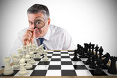 Businessman with magnifying glass with chessboard — Stock Photo
