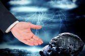 Businessmans hand presenting against large rock — Stockfoto