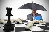 Businessman under umbrella with chessboard — Stock Photo