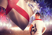 Football player holding ball against fireworks — Stockfoto
