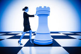 Businesswoman pushing chess piece — Stockfoto