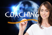 Businesswoman writing word coaching — Stock Photo