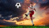 Football player in white kicking — Photo