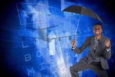 Businessman cheering and holding umbrella — Stock Photo