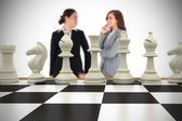 Businesswomen and chess pieces — Stock Photo