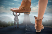 Cowboy boots stepping on businessman — Stock Photo