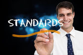 Businessman writing word standards — Stockfoto