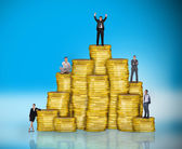 Business people on pile of coins — Stock Photo