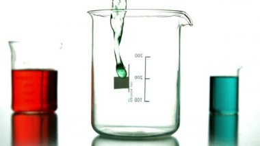 Green liquid pouring into beaker — Video Stock