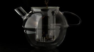 Loose tea pouring into glass teapot — Stock Video