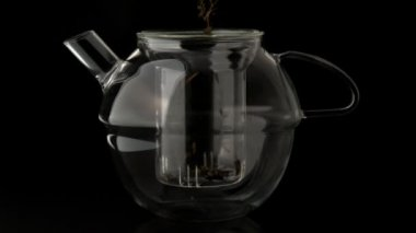 Loose tea pouring into glass teapot — Stockvideo