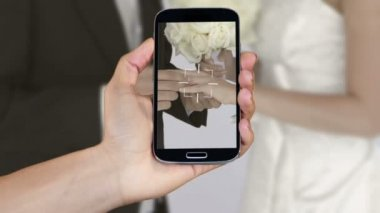 Hand showing wedding clips on smartphone — Stockvideo